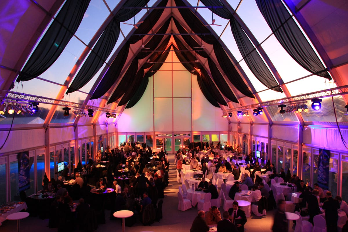 Carpa grande con techo acabado en punta e iluminaria interior para eventos y cenas profesionales